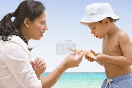 Hispanic mother and son looking at starfish