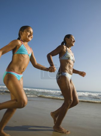 Hispanic mother and daughter running