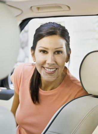 Hispanic woman sitting in car
