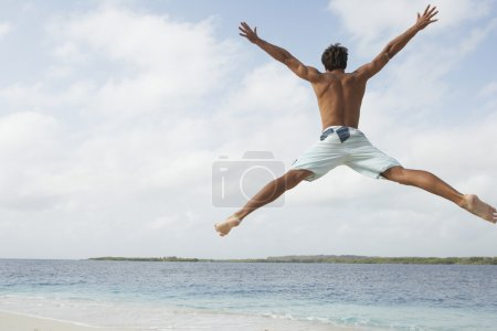 South American man jumping on beach