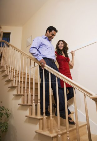 Multi-ethnic couple walking down stairs