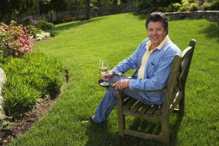 Hispanic man holding drink in backyard