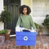 African girl holding recycling bin