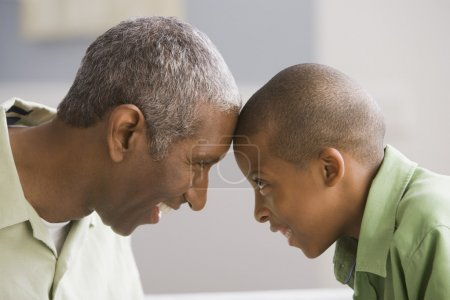 African American grandfather and grandson touching foreheads