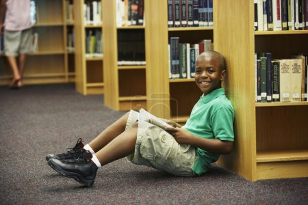 African American boy holding library book