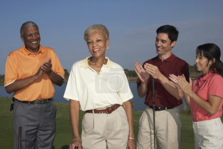 Friends clapper for senior woman on golf course