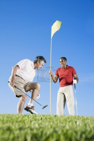 Multi-ethnic men playing golf