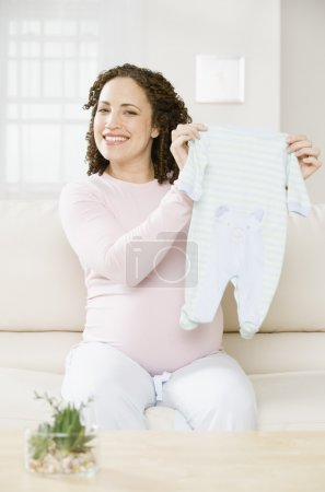 Pregnant African woman holding up baby clothes