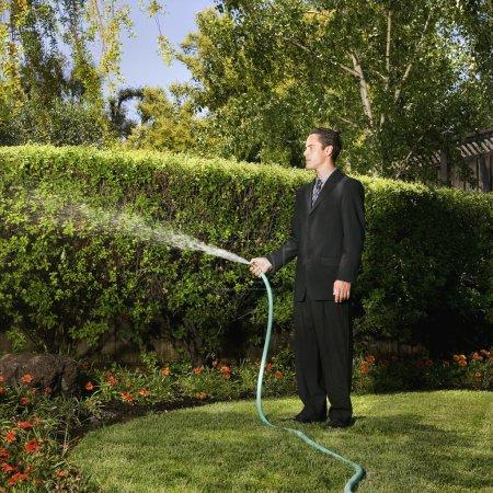 Hispanic businessman watering plants