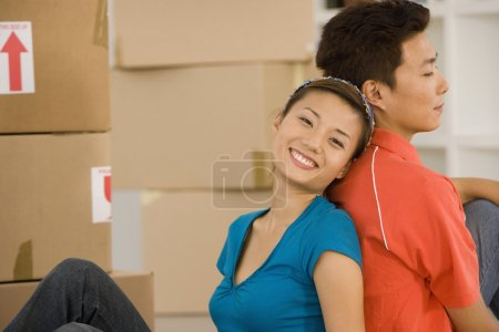 Asian couple sitting back to back next to moving boxes