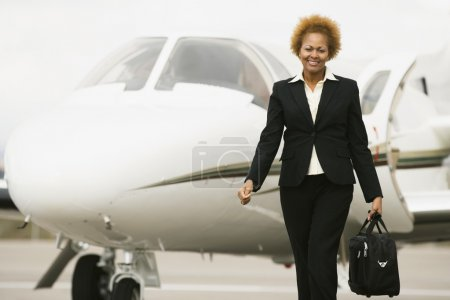 African American businesswoman walking away from airplane
