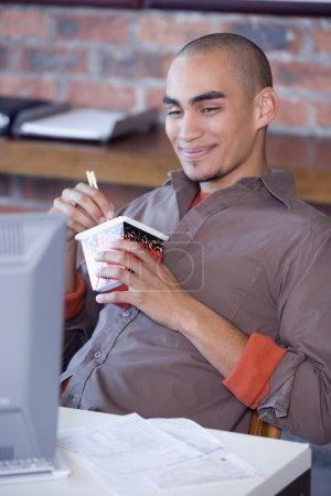African American man eating take out food