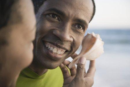 African man listening to seashell