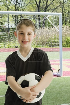 Mixed Race girl holding soccer ball