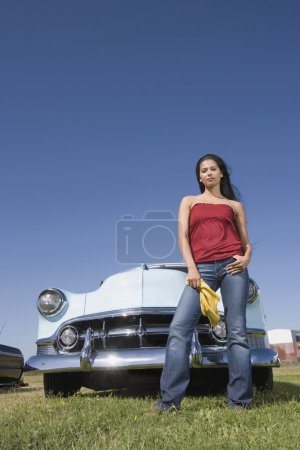 Mixed Race woman in front of low rider car