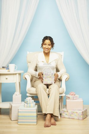 Pregnant Mixed Race woman holding gift