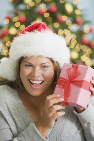 Hispanic woman holding Christmas gift