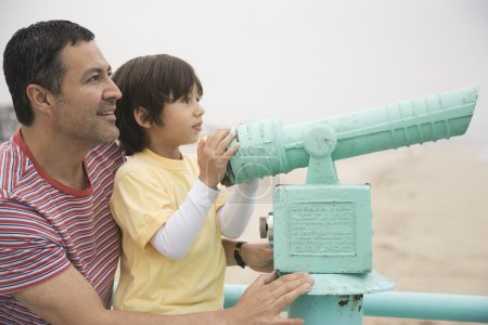 Hispanic father and son with telescope