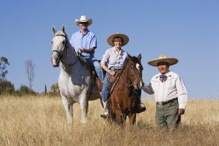Hispanic man leading couple on horses