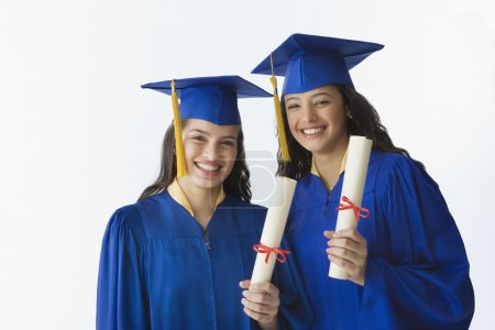 Female graduates holding diplomas