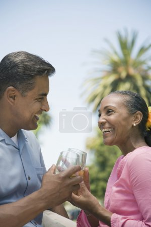 Multi-ethnic couple toasting outdoors