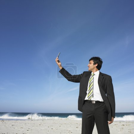 Hispanic businessman looking at cell phone at beach