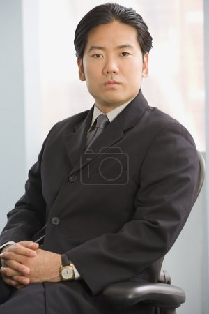 Asian businessman sitting in chair