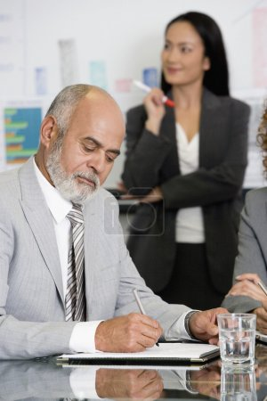 Senior African businessman writing at table