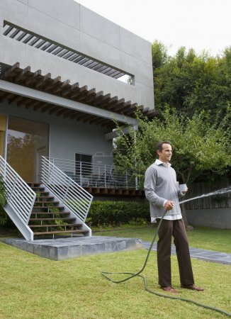 Man watering lawn in front of house