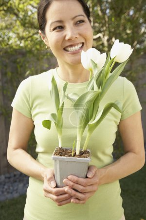 Asian woman holding potted tulips