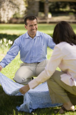 Hispanic couple laying down picnic blanket