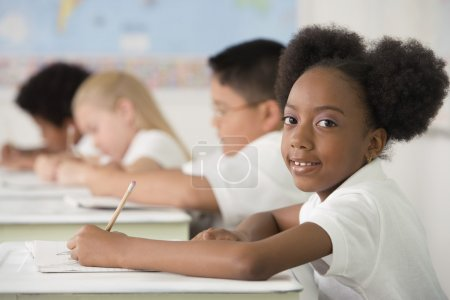 Children writing at desks in classroom