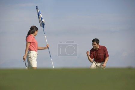 Hispanic couple playing golf