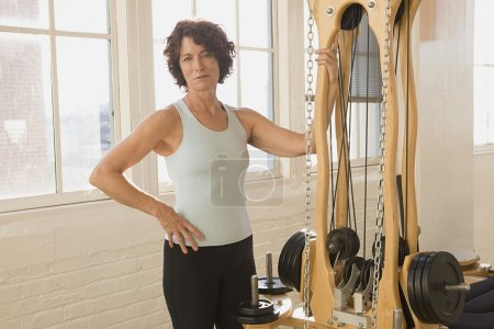 Senior woman standing next to exercise equipment