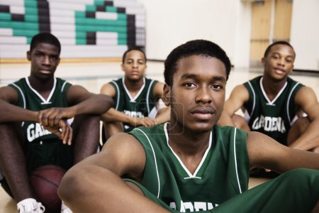 African basketball players sitting in gym
