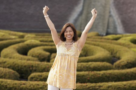 Asian woman with arms raised
