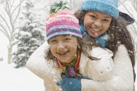 Multi-ethnic girls hugging in snow