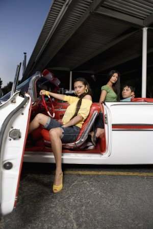 Hispanic woman sitting in convertible