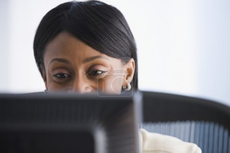 African American businesswoman looking at computer
