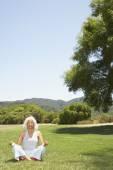 Senior Hispanic woman meditating in park