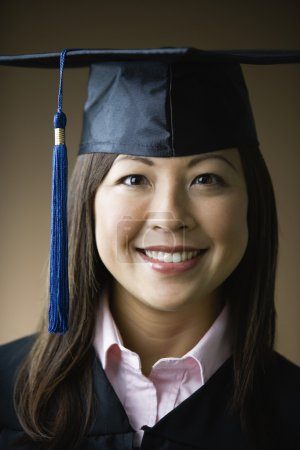 Asian woman wearing graduation cap and gown