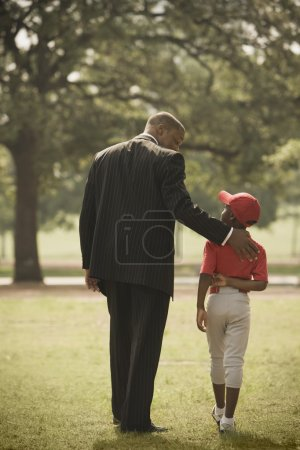 African businessman with son in baseball uniform