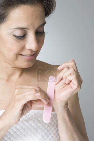 Hispanic woman filing fingernails