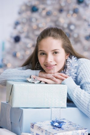 teenaged girl leaning on Christmas gifts