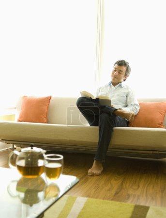 Hispanic man reading on sofa