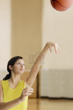Hispanic teenaged girl shooting basketball