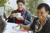 Multi-ethnic women having coffee outdoors