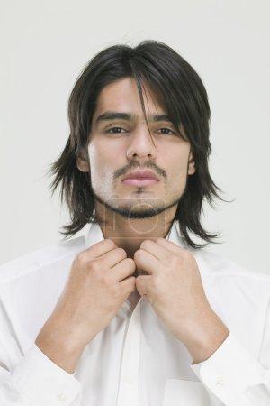 Young Hispanic man buttoning shirt