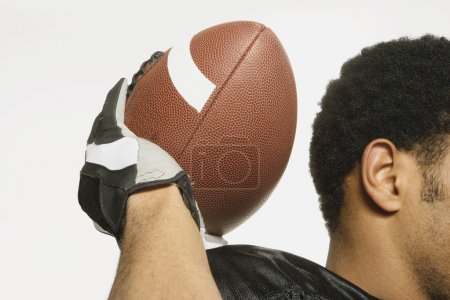 African American man holding football