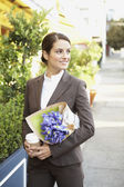 Hispanic businesswoman carrying flowers